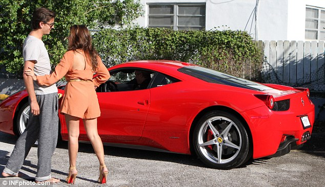Celebrating: The couple could not contain their excitement as they took delivery of a brand new red Ferrari