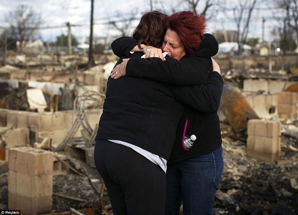 Fire damage: Neighbors Lucille Dwyer (right) and Linda Strong (left) embrace after looking through the wreckage of their homes in Breezy Point, Queens, New York