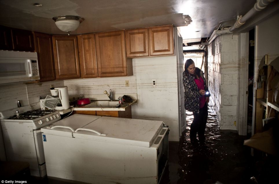 Jackie Hoey inspects the first floor of her home which experienced heavy flooding due to Hurricane Sandy in Long Beach, New York