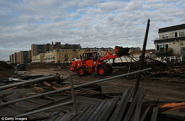 A front loader moves debris in Rockaway neighborhood: Most major bridges have reopened but will require three occupants in the vehicle to pass