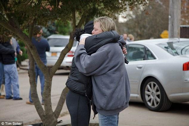 'He was my rock': Christine Filipowicz hugs a friend outside her home
