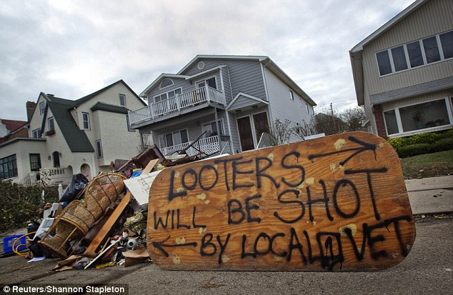 Vigilante justice: A sign is seen outside a home in Long Beach in Long Island on November 2 gives a dire warning to would-be looters