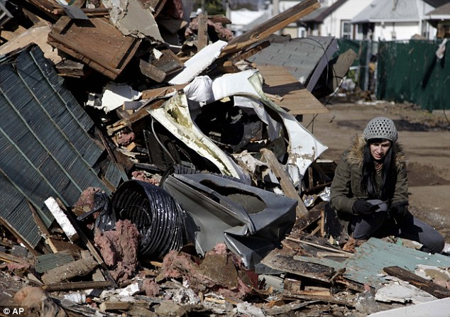 What remains: Julie Traina tries to recover some personal items from the destroyed home of her parents in Staten Island yesterday