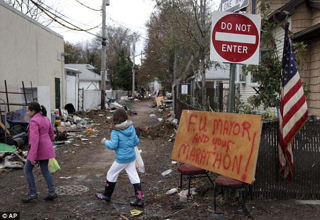 Bitter: A sign about the marathon and New York City Mayor Michael Bloomberg is displayed in a devastated section of Staten Island yesterday, before the marathon was canceled