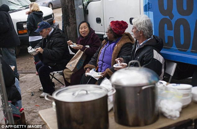 Relief: People eat soup at a donation and distribution center in the Rockaways, though residents are complaining there is not enough assistance for them