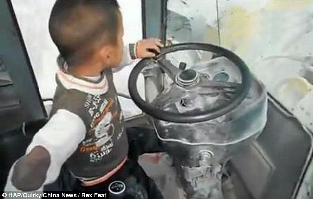 Five-year-old Wang Shuhan operating the machine of his father's digger in Wuhan, Hubei Province, China
