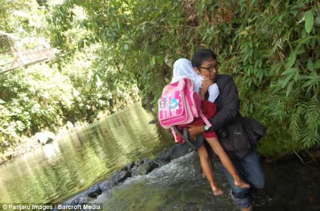 The school run: A man carries his daughter through the water to take her to school because there is no road access to the village