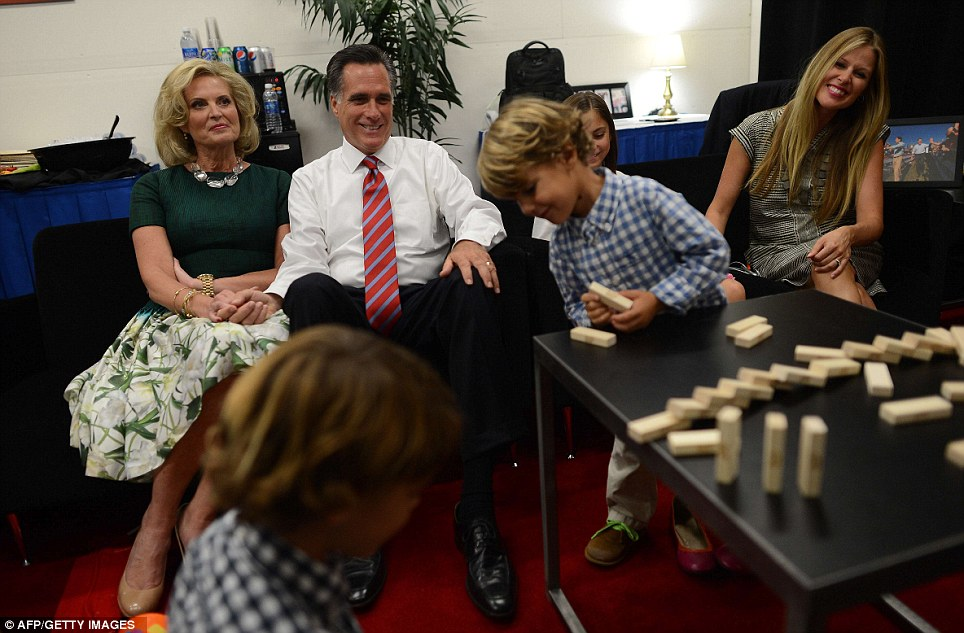 Together: Despite Obama's young daughters not been seen in public during the campaign, Mitt Romney was often pictured with his family. He is pictured watching his grandchildren play Jenga before the final presidential debate