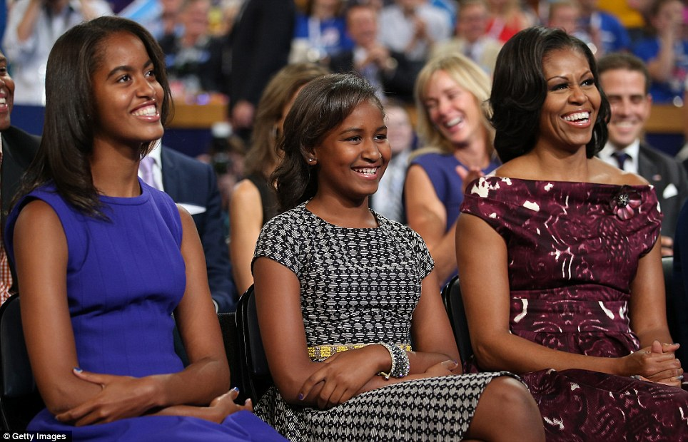 Funny: Malia, left, and Sasha, right, and First Lady Michelle listen as their father speaks at the Democratic National Convention