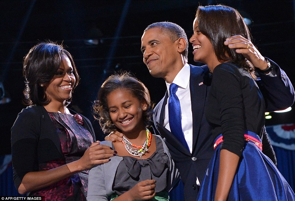 Delighted: Sasha, second left, and Malia, right, looked thrilled on stage last night with their mother Michelle and victorious father