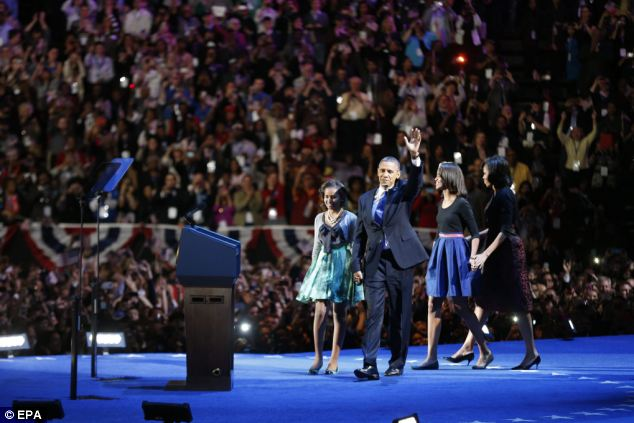 Four more years: The Obamas wave to the crowd after the victory was called at 11.15pm on Tuesday