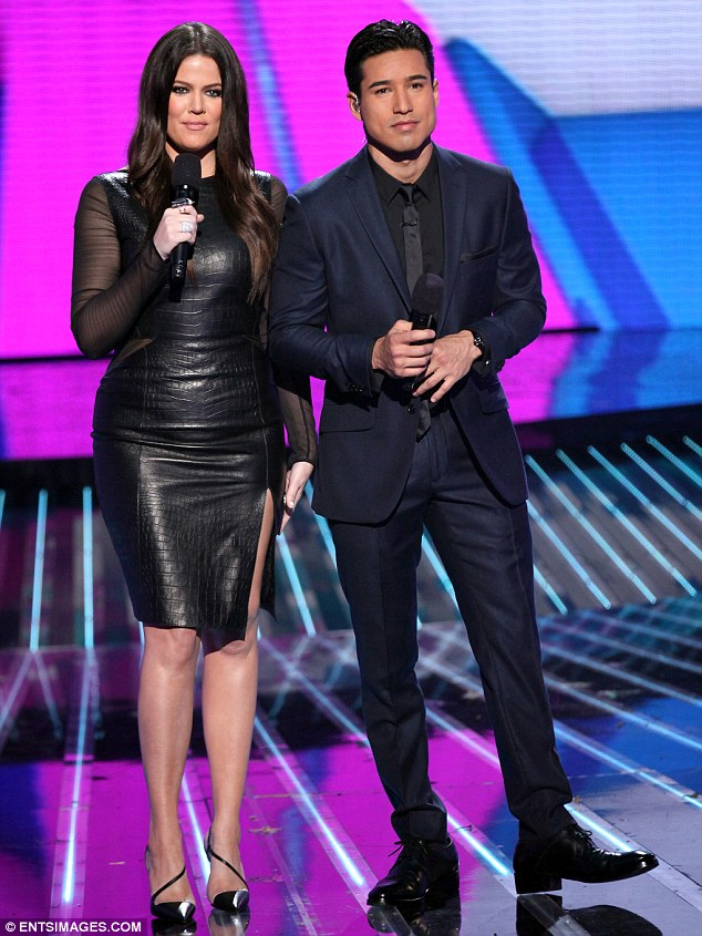 Sultry star: Khloe Kardashian, pictured with Mario Lopez, slipped her curves into a chic crocodile skin look dress that featured sheer sleeves