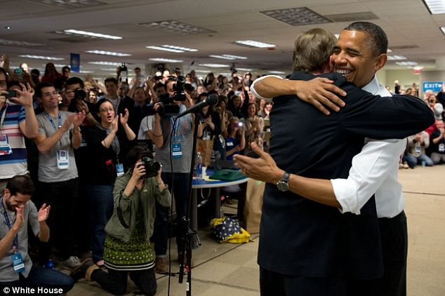 Minutes before: Obama is seen smiling as he hugs Jim Messina shortly before making his remarks