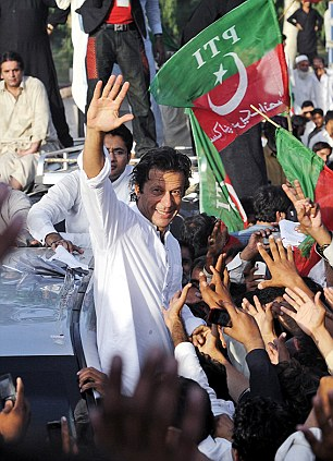 Support: Imran Khan, who heads the opposition political party Tehrik-e-Insaf, waves to supporters during a 'peace march' against US drone attacks