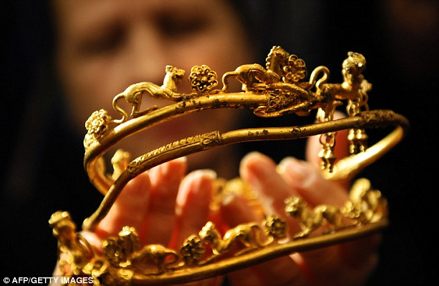 Touching history: An archaeologist displays a gold tiara engraved with a lion's head and other animals found at the Bulgarian tomb. It is part of an incredible and historically-significant haul