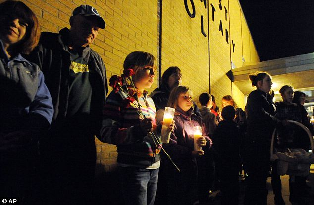 Silent night: A crowd gathers during a candlelight vigil at Southwest Elementary School in Greenwood, Indiana, for a second-grade teacher believed to have died in the fire