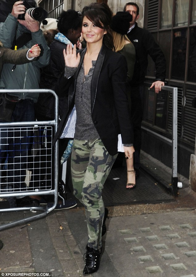 Military chic: Cheryl Cole showed off her slim figure in a pair of skintight camouflage trousers as she arrived at the BBC Radio 1 studios alongside her Girls Aloud bandmates on Monday morning