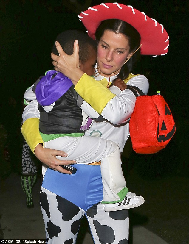 Devoted mommy: Sandra carries a sleepy Louis home after his exciting Toy Story themed Halloween in Studi City, California