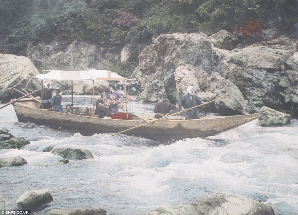 Braving the rapids: Ladies travelling along a dangerous mountain river in a wooden boat