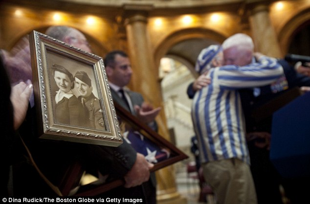 Never forgotten: Stephan Ross (pictured in striped jacket) hugs family of soldier Steven Sattler who liberated him from Dachau concentration camp, 67 years ago. Left, a picture of the late Mr Sattler