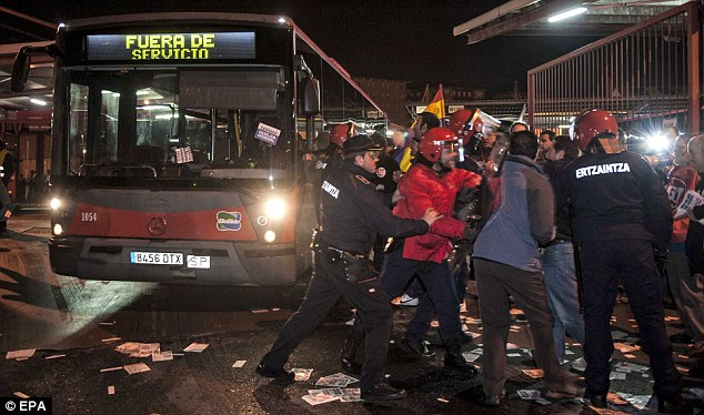 Pickets clash with police as they try to prevent buses from leaving a depot in Bilbao, northern Spain