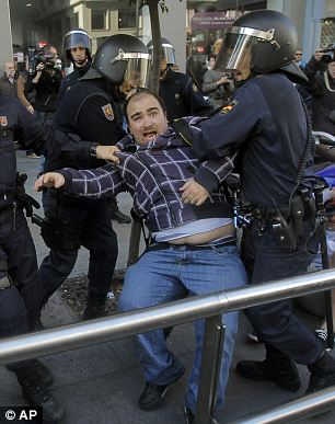 Riot police apprehend a protestor during a general strike in Madrid, Spain, Wednesday,