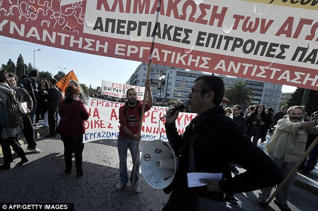 A protest leader outside the Greek parliament building in Athens uses a megaphone to rally other demonstrators