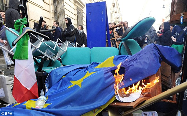 Protesters burn an EU flag after storming the regional Palace of the Province in Turin and piling furniture onto the street