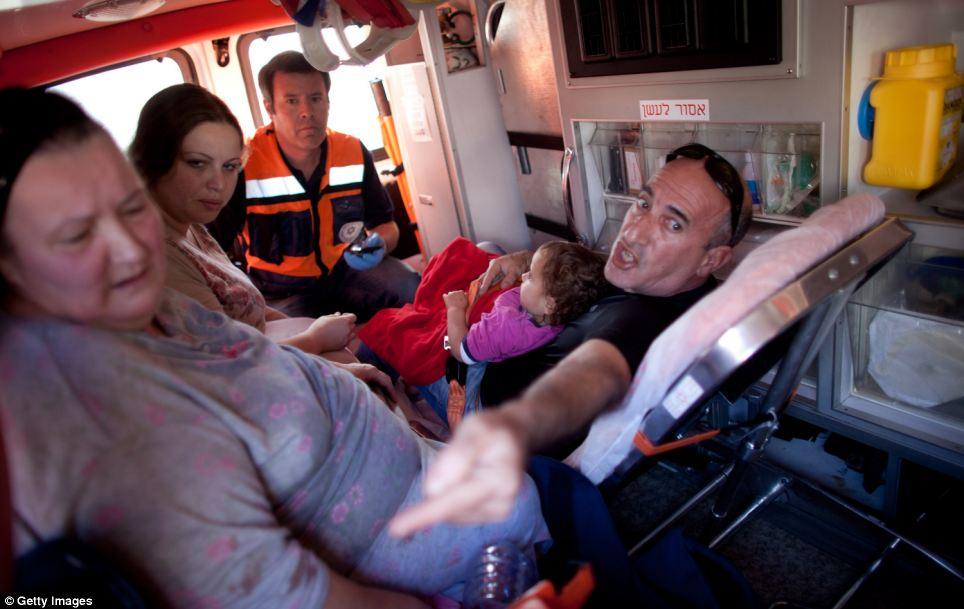 Medical help: Israelis are evacuated in an ambulance after a rocket attack from Gaza which hit an apartment building, claiming three lives