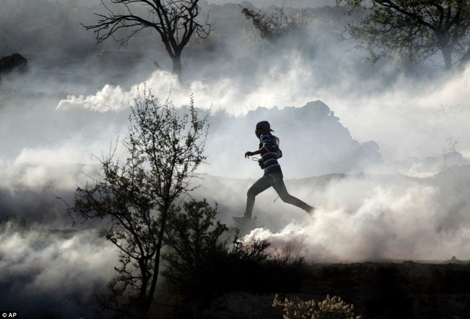 Protest: A Palestinian demonstrator runs through a cloud of tear gas during clashes against Israel's operations in Gaza Strip, outside Ofer, an Israeli military prison near the West Bank city of Ramallah