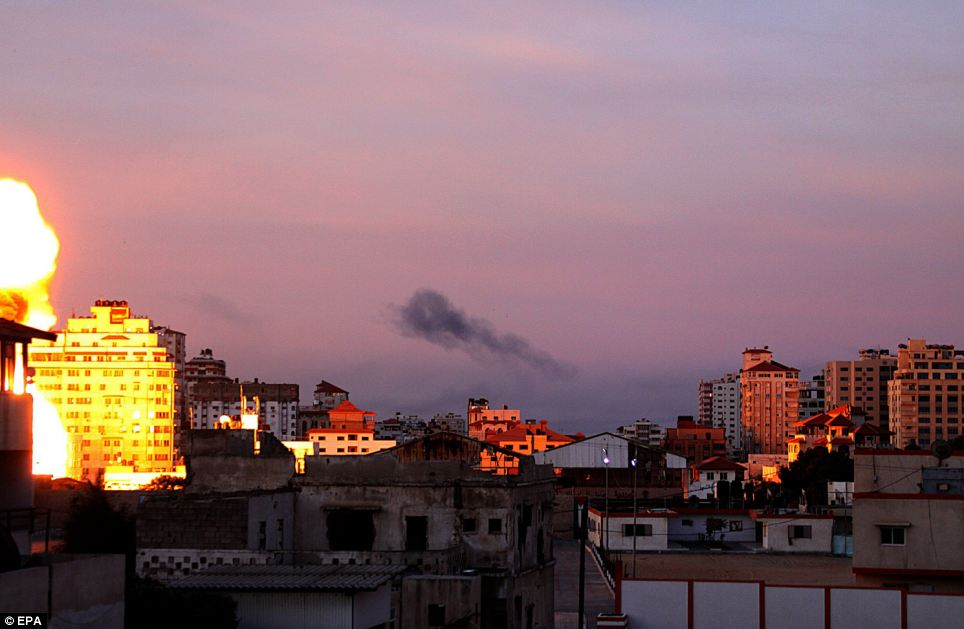 Burning: Fire rises from a Hamas site after an Israeli air strike in the central of Gaza city at dawn this morning