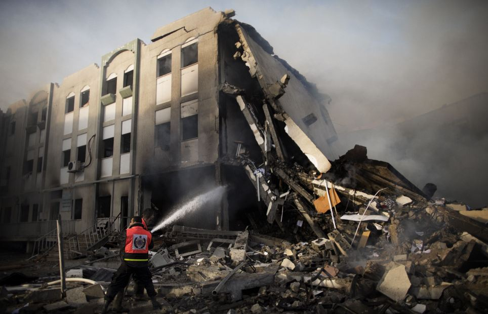 Burning: Palestinian firefighters try to extinguish a fire at the Civilian Affairs branch of the Ministry of Interior following an Israeli air raid