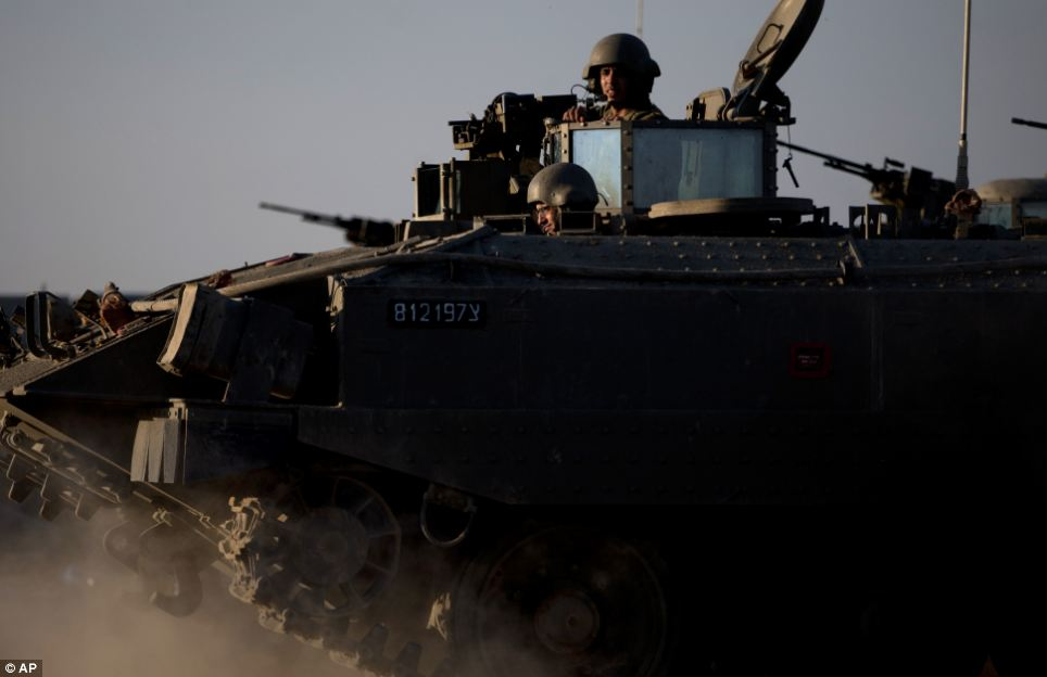 Show of strength: Israeli soldiers ride on top of an armored personnel carrier close to the Israel Gaza Border, southern Israel