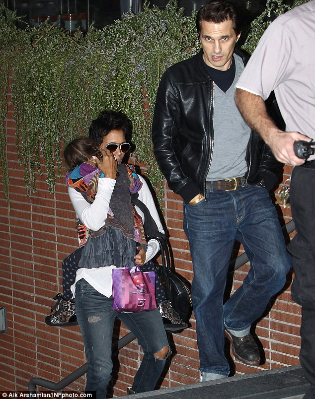 Protective: Nahla keeps her head burrowed firmly in her mother's neck as they walk to the movies