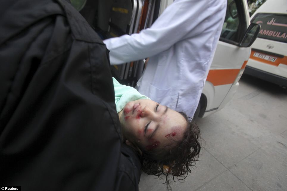 Casualty: A wounded Palestinian child is carried into a hospital after an Israeli air strike in the northern Gaza Strip
