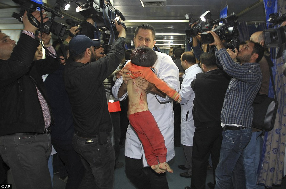 Casualty: A medic carries the body of a Palestinian boy allegedly killed in an Israeli air strike to an event attended by Hamas Prime Minister Ismail Haniyeh and Egyptian Prime Minister Hesham Kandil