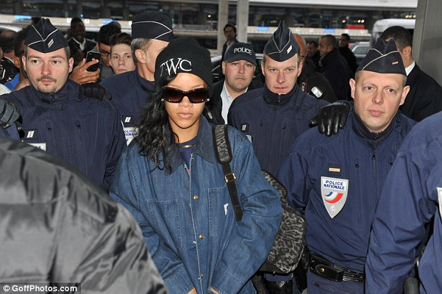 And she's off again: Rihanna is escorted by the French police to the airport ahead of her flight to Berlin