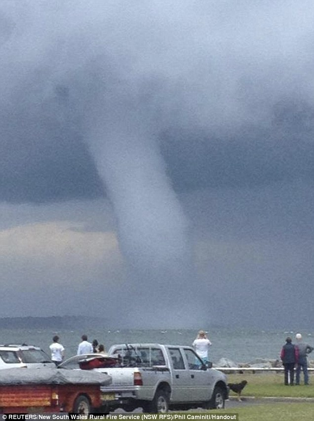 Too close for comfort: People look at the waterspout near to the shoreline at Batemans Bay