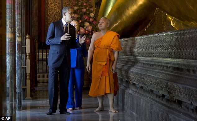 Spiritual: Obama and Secretary of State Hillary Clinton tour the Viharn of the Reclining Buddha with Chaokun Suthee Thammanuwat