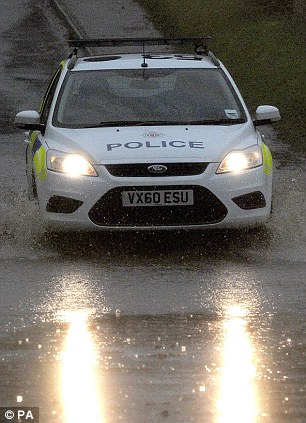 Mind how you go: A police car edges through floodwater in Coates, Gloucestershire on Wednesday