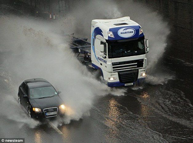 Surfing: A wall of water thrown up by a lorry hits an Audi as it struggles to overtake on the M5 in Birmingham on Wednesday