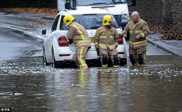 Helping hands: Fire fighters push a car out of floodwater near Tetbury, Gloucestershire, on Wednesday as the rain continued to fall