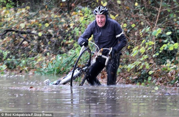 Off road: A man picks up his bicycle after falling off it into flood water along Watery Lane near Knowle, West Midlands on Wednesday