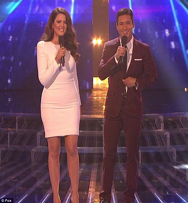 White hot: Khloe looked great in a fitted white long-sleeve mini dress as she took to the stage with Lopez