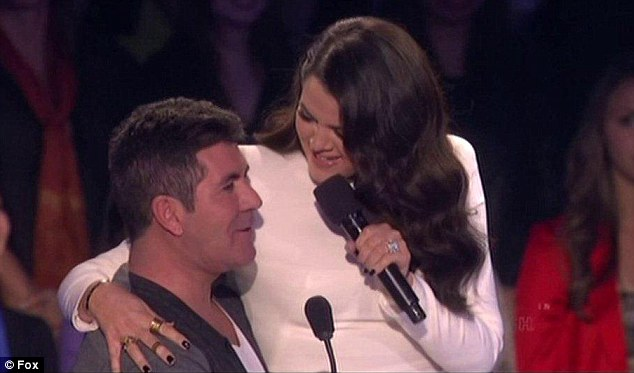 Flirt factor: Khloe Kardashian made Simon Cowell turn a shade of bright red when she sat on his lap during the live X Factor USA show on Wednesday night