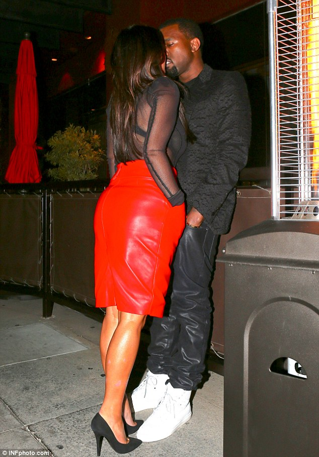 Pucker up: Kim Kardashian gives boyfriend Kanye West a sneaky kiss in a Beverly Hills restaurant on Tuesday