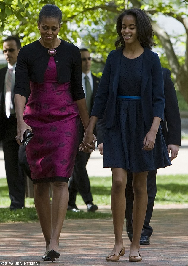 Look-a-likes: Malia, standing nearly as tall as her 5-foot-11 mother, now carries herself with confidence, striding alongside her mother like two-peas-in-a-poised-pod