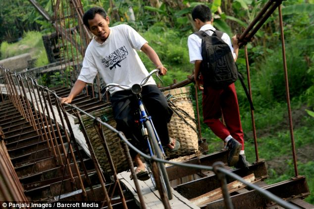 Way of .ife: People cross the aqueduct that separates the two villages in Indonesia