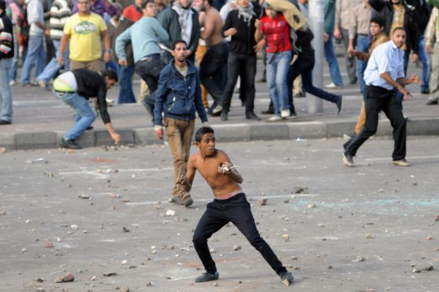 A young man throws stones during a clash in the Mediterranean city of Alexandria