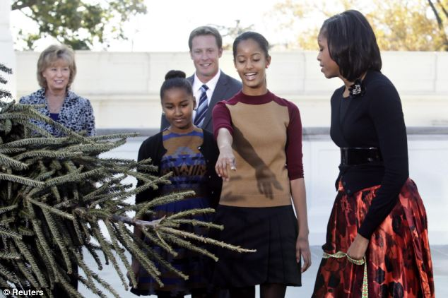 Impressed: Malia points at the tree as they accept it from the champion farm in North Carolina